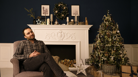 Bearded handsome hipster young man in Christmas roomthinking of gift ideas. Daydreaming. Banco de Imagens