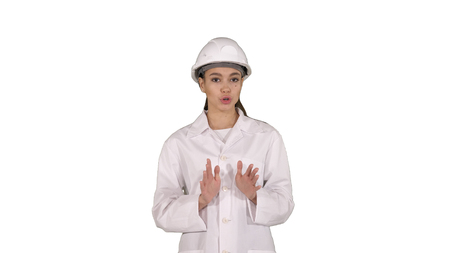 Female engineer walking and talking to camera presenting something on white background.