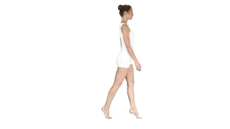 The young woman walking on her tip-toes on white background.
