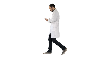Male doctor walking and using mobile phone on white background. Imagens
