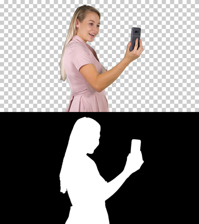 Female in pink dress making video call with her smart phone, Alpha Channel