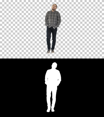 Young man walking with hands in his pockets and whistles, Alpha Channel