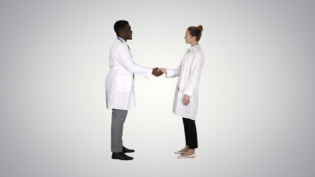 Nice to meet you Doctors meet and shake hands on gradient background.