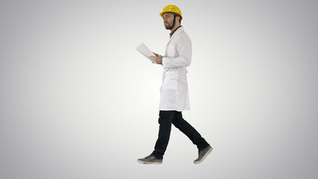 Engineer manager walking with hard hat is holding paper and checking on gradient background.