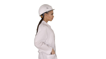 Woman in white robe putting hard hat on while walking on white background.