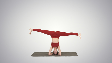 Woman performing a headstand with split on gradient background.