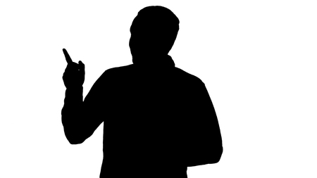 Medium shot. Silhouette Handsome young man walking and looking to the camera and pointing to the sides showing something. Professional shot in  resolution. 004. You can use it e.g. in your commercial video, business, presentation, broadcast