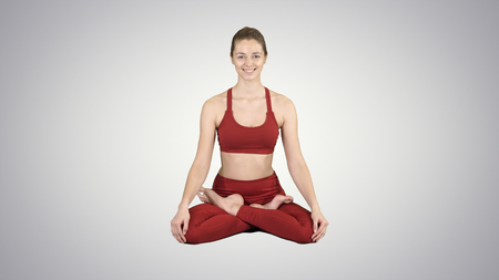 Young smiling woman practicing yoga, doing Padmasana exercise, Lotus pose on gradient background. 写真素材