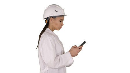 Engineer using mobile phone texting while walking on white background.