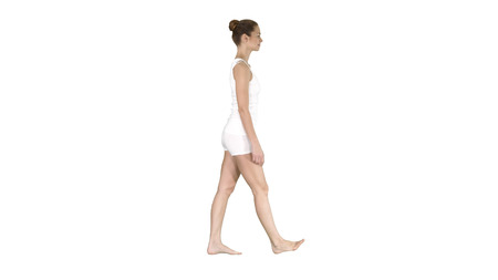 One female walking barefoot in white clothes on white background.