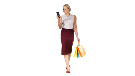 Beautiful attractive women looking in smartphone and holding shopping bags while walking on white background.