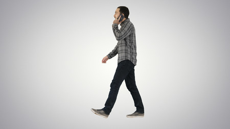 Young bearded man walking and talking on the mobile phone on gradient background. Zdjęcie Seryjne