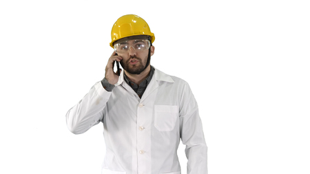 Engineer in protective glasses and hat walking, taking on the phone on white background.