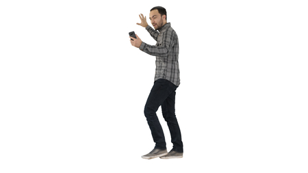 Handsome bearded man recording vlog blog with smartphone while walking on white background.