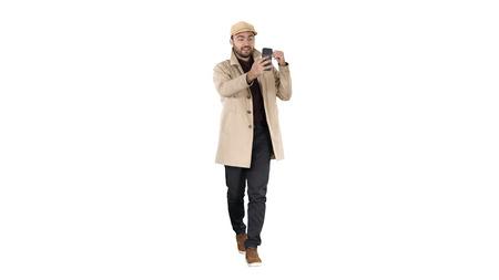 Autumn fashion style man recording video blog walking on white background.