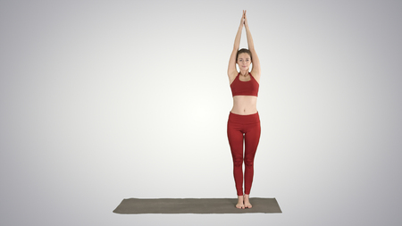Sporty young woman doing yoga practice on gradient background.