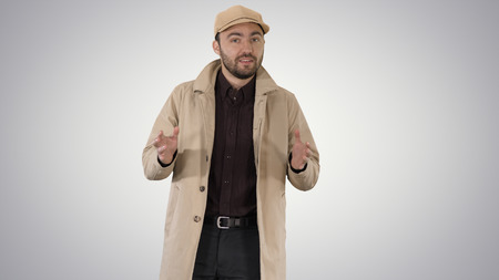 Charming man in trench coat walking and talking to camera on gradient background.