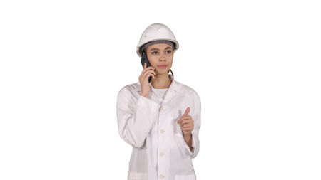 Woman engineer talking on the phone while walking on white background.