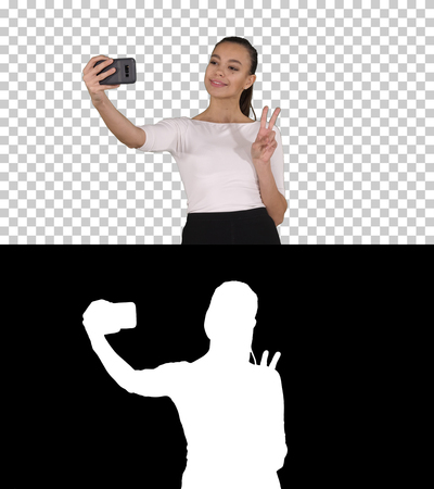 Smiling attractive woman taking a selfie while walking, Alpha Channel 版權商用圖片