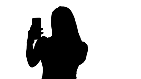 Silhouette Happy woman takes selfie photo with mobile phone.