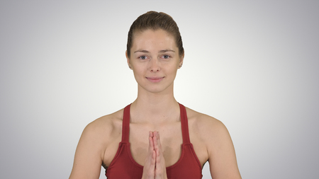 Caucasian woman yoga meditating sitting lotus, hands coupled on gradient background.