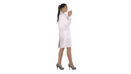 Female doctor drinking coffee and walking on white background.