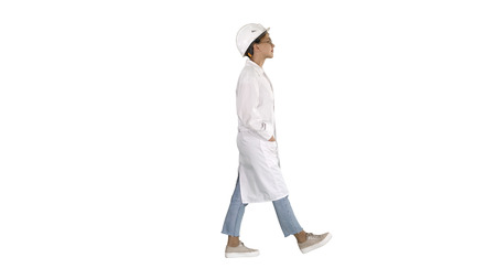 Walking woman engineer with hands in pockets on white background. 写真素材