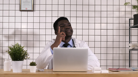 African man doctor pointing finger up having an idea. Professional shot in 4K resolution. 017. You can use it e.g. in your commercial video, medical, business, presentation, broadcast Imagens