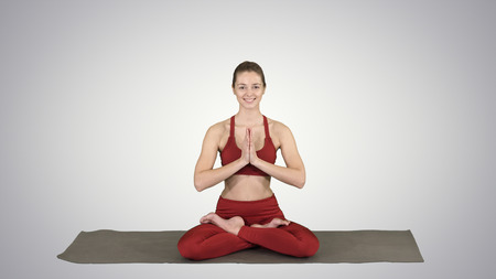 Smiling woman yoga meditating sitting lotus, hands coupled on gradient background. Reklamní fotografie - 120872815