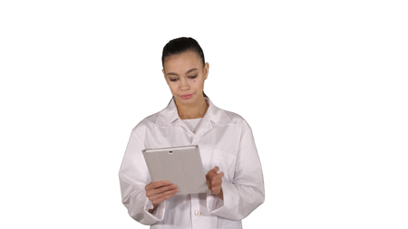 Doctor using tablet while walking on white background.