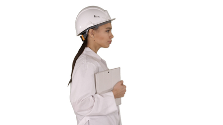 Attractive Hispanic woman in white lab coat and white safety hard hat walking holding notebook or tablet on white background.