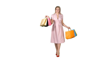 Young blonde girl in pink dress showing to camera shopping bags and walking on white background.