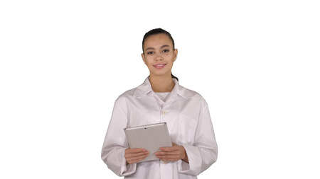 Happy female doctor using tablet computer swiping pages on it on white background.
