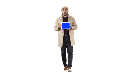 Young man walking, talking and showing digital tablet with blue screen mockup on white background. Stockfoto