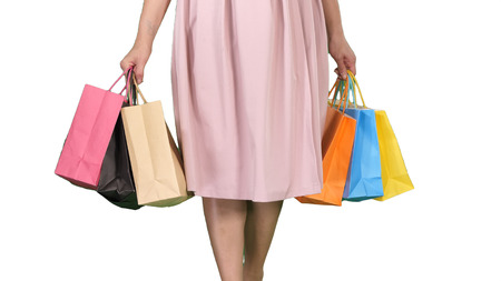 After day shopping Young woman carrying shopping bags while walking on white background. Stockfoto