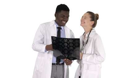 Laughing doctors studying X-ray on white background.