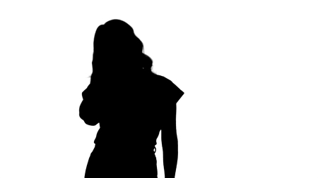 Medium shot. Silhouette Young attractive happy model standing and smiling. Professional shot in 4K resolution. 006. You can use it e.g. in your commercial video, business, presentation, broadcast