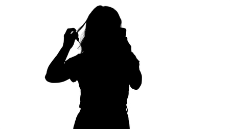 Medium shot. Silhouette A nice young woman straightens her hair looking in the mobile. Professional shot in 4K resolution. 006. You can use it e.g. in your commercial video, business, presentation, broadcast