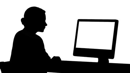 Back view to the monitor of the computer. Silhouette Young woman working in office, sitting at desk, looking at monitor. Professional shot in 4K resolution. 007. You can use it e.g. in your commercial video, business, presentation, broadcast Stockfoto