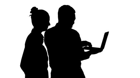 Coup moyen. Conseiller d'affaires afro-américain de silhouette montrant quelque chose sur l'écran d'un ordinateur portable parlant à une femme d'affaires blanche. Prise de vue professionnelle en résolution 4K. 012. Vous pouvez l'utiliser par exemple dans votre vidéo commerciale, médicale, commerciale, présentation, diffusion
