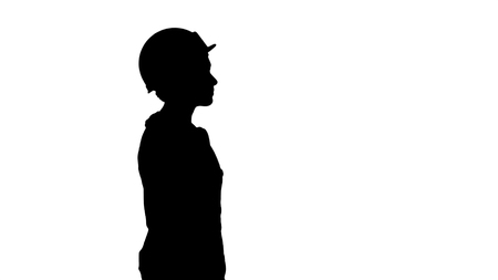 Medium shot. Side view. Silhouette Construction worker lady walking emotionless. Professional shot in 4K resolution. 006. You can use it e.g. in your commercial video, business, presentation, broadcast