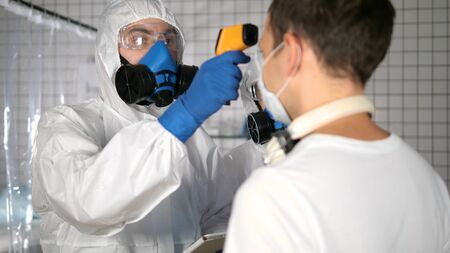 Doctor in protective suit using pyrometer to measure temperature of people in a hospital.