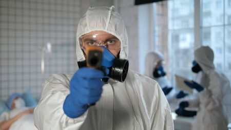 Male doctor in a protective suit holding an digital infrared thermometer measuring temperature to the camera.