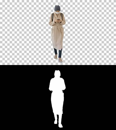 Woman dressed in a coat wearing medical mask using phone and walking, Alpha Channel