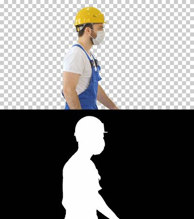 Construction worker wearing a hardhat and mask walking, Alpha Channel