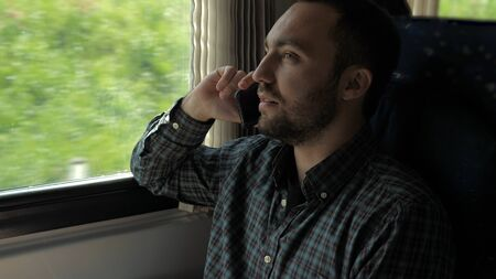 Handsome man talking on mobile phone in train.