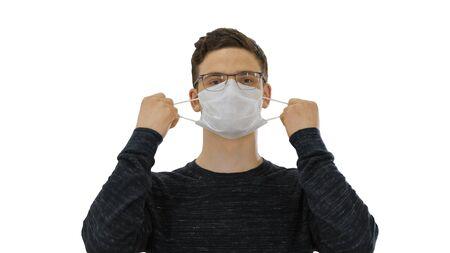 Joyful happy man taking off his protective mask The coronavirus pandemic epidemic is over on white background.