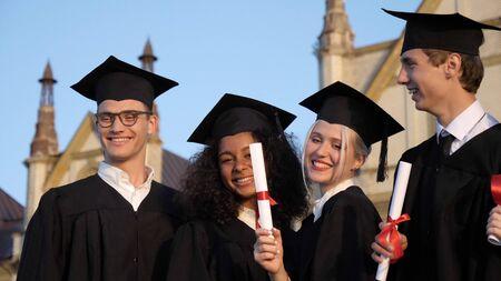 Estudiantes graduados sonriendo y riendo con diplomas.