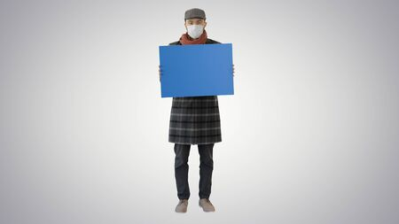 Man in a trendy outfit and medical mask holding blank placard on gradient background.