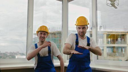 Builders funny dance in helmets. Фото со стока